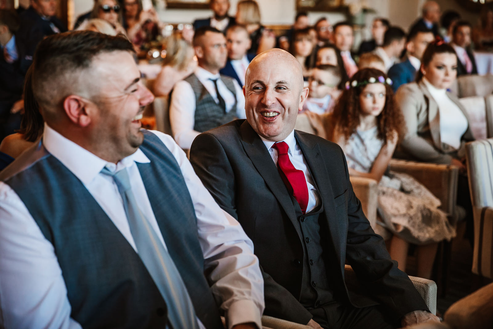Wedding guests laughing during the ceremony