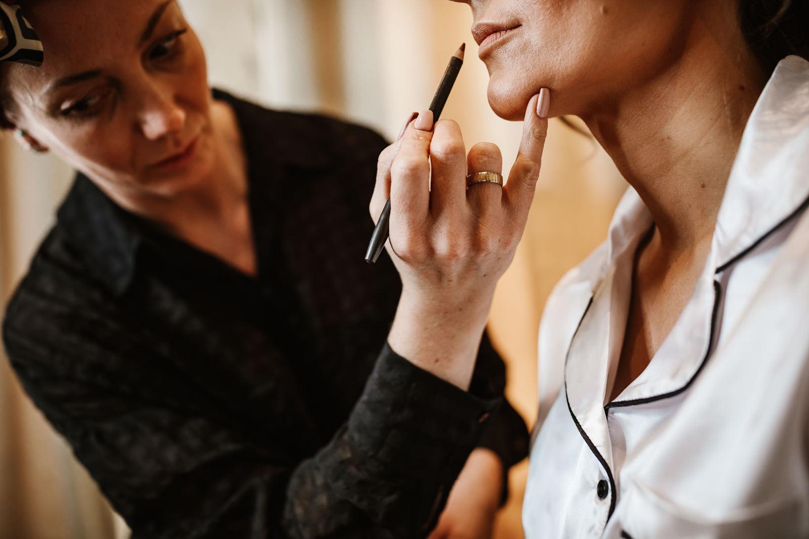 Bride having lip gloss applied