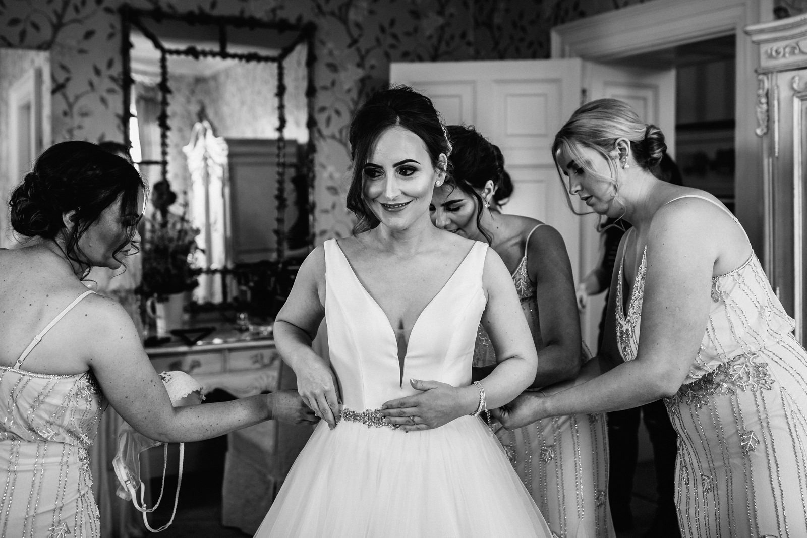 Bride getting helped into her dress at Eaves Hall