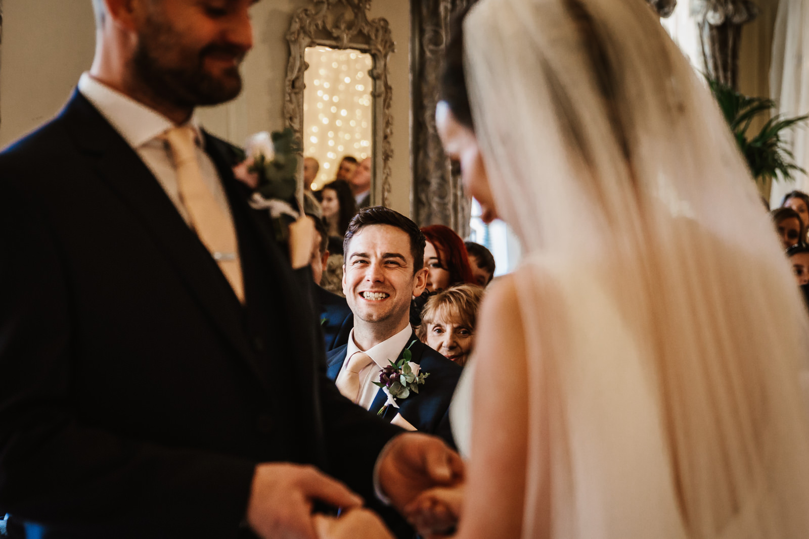 Best man smiling during ceremony