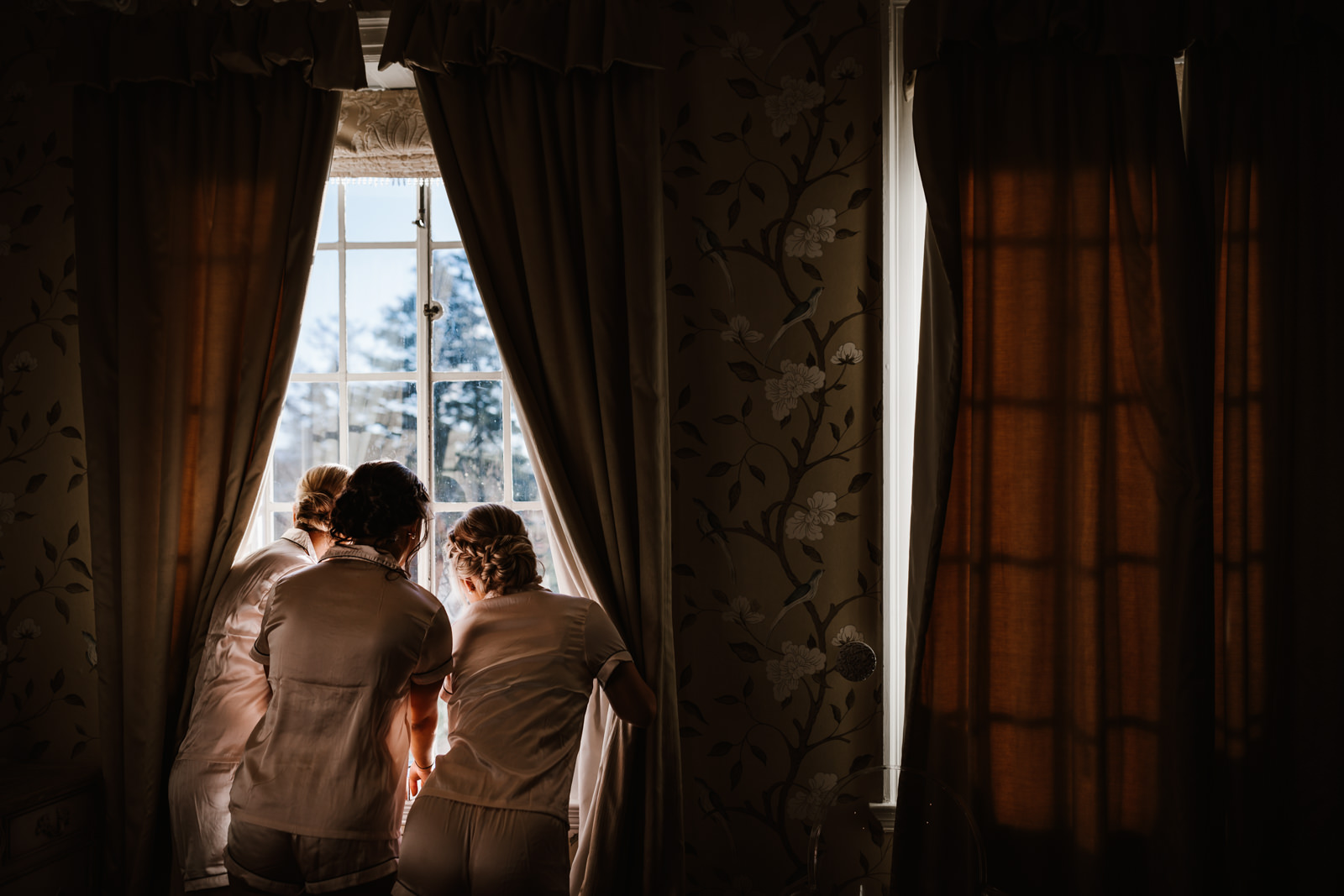 Bridesmaids looking through the window at eaves hall