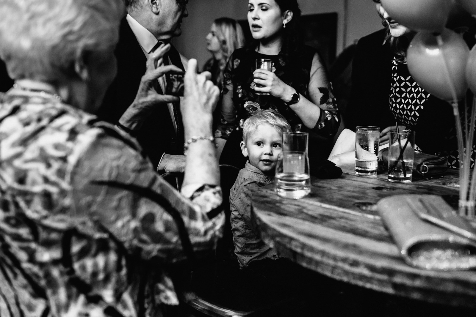 Little boy sat at the table with guests