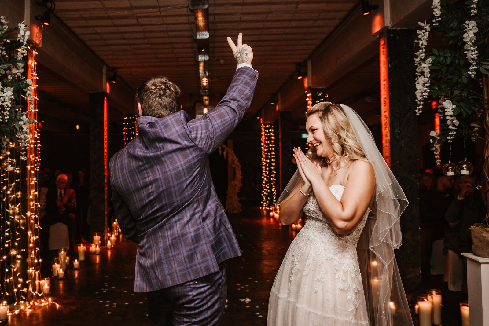 Groom gives peace sign to wedding guests