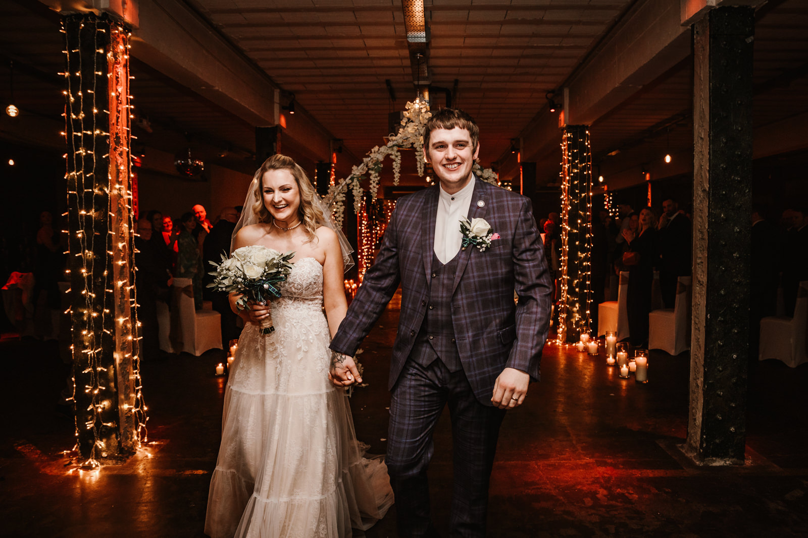 Married couple walk down the aisle at Victoria Warehouse