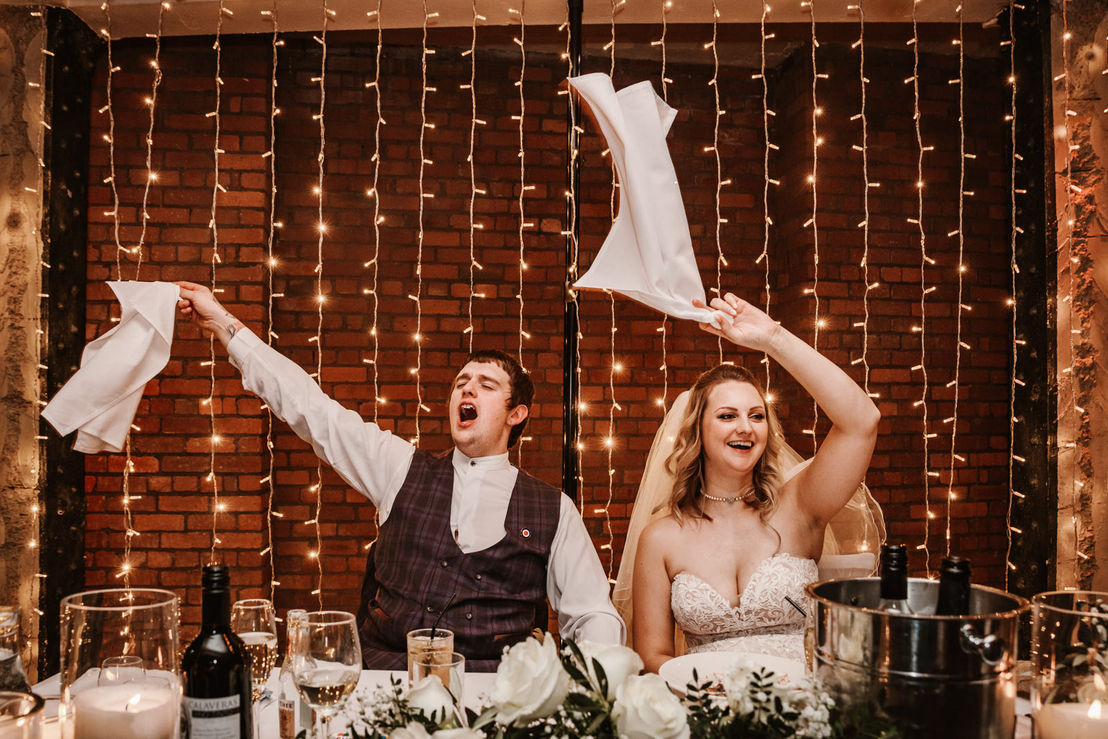 Bride and groom waving napkins at Victoria warehouse