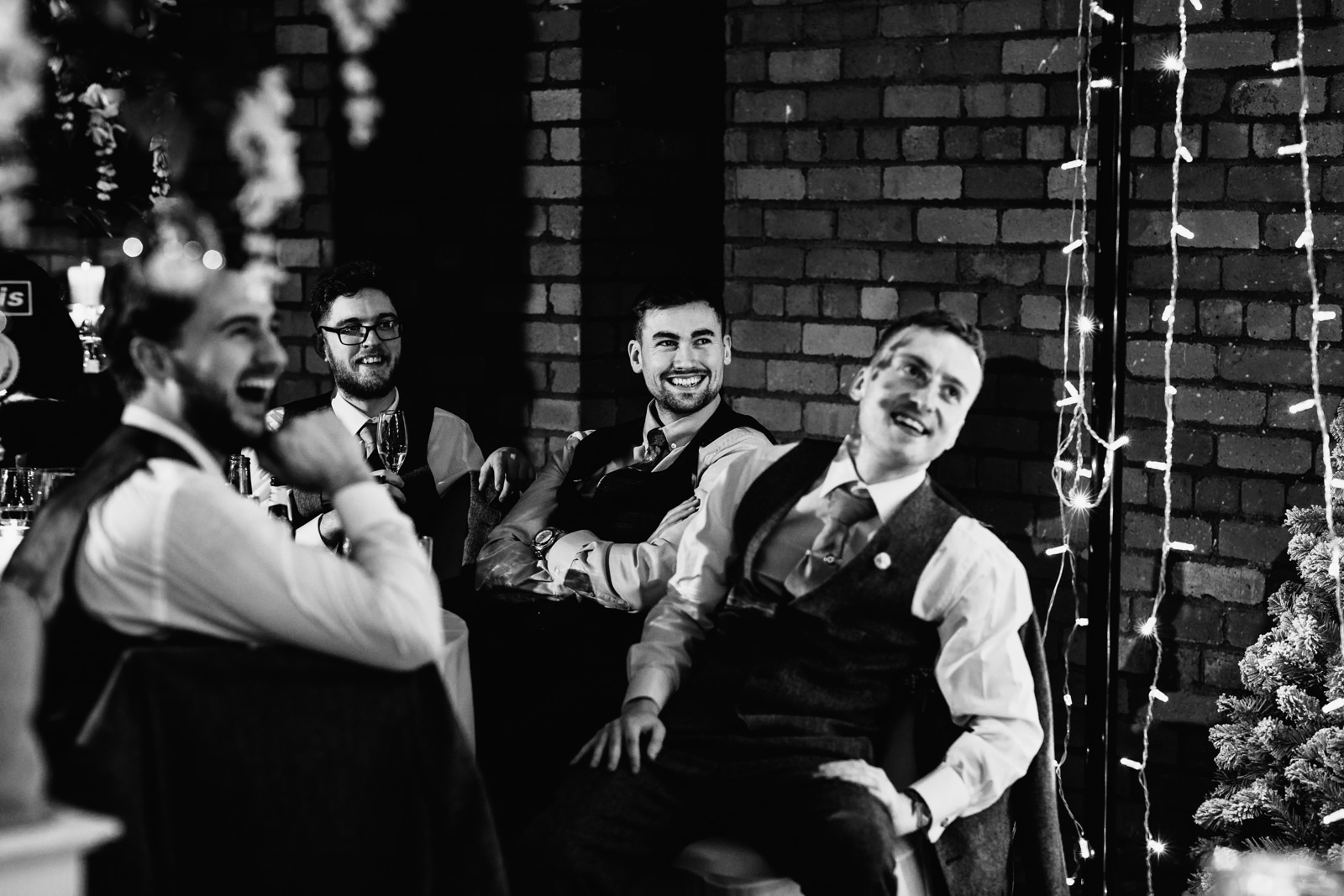 Wedding party laughing during speeches