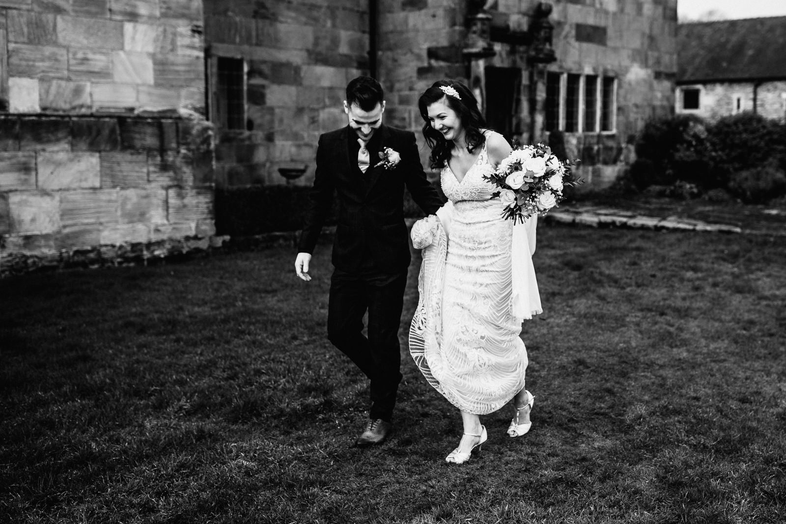 bride and groom walking through the gardens at The Ashes Barns
